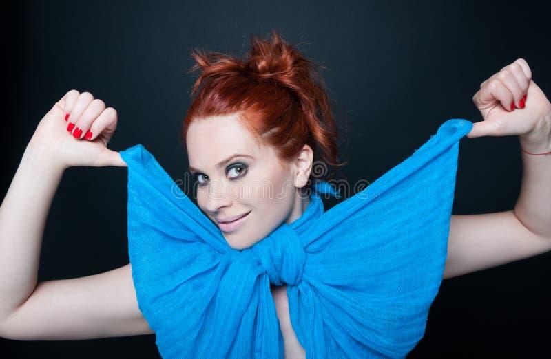 Jeune modèle attrayant utilisant l'écharpe bleue photo libre de droits