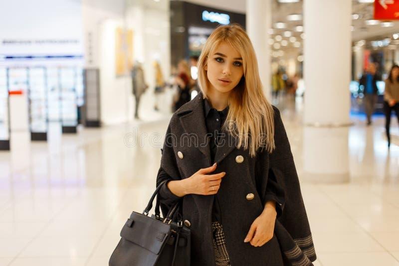 Jeune modèle blond sexy de femme dans un manteau à la mode chic avec un sac à main noir en cuir à la mode de mode image libre de droits