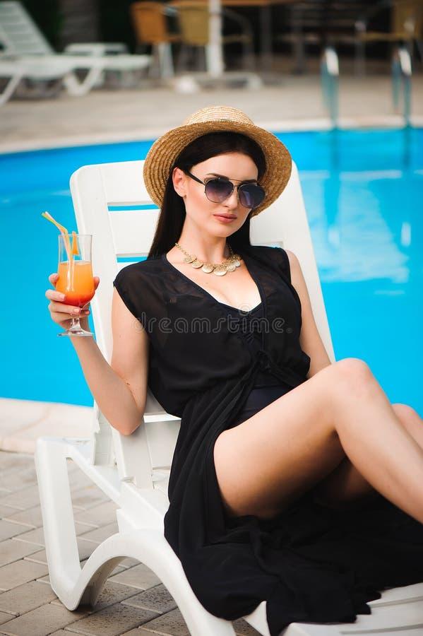 Jeune modèle bronzage dans l'équipement élégant d'été appréciant la réception au bord de la piscine, tenant le cocktail savoureux photographie stock libre de droits