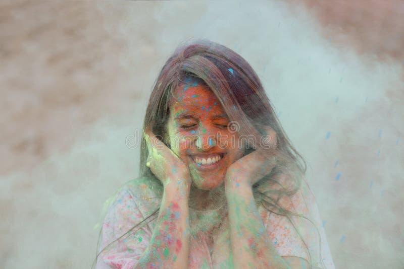 Jeune modèle drôle ayant l'amusement dans un nuage de peinture sèche verte, célébrant le festival de couleurs de Holi au désert images stock