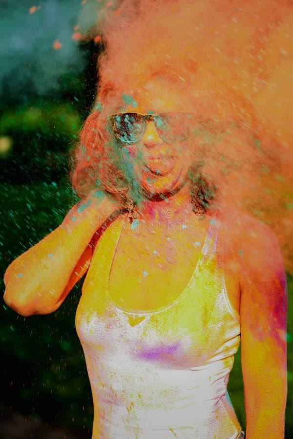 Jeune modèle drôle ayant l'amusement dans un nuage de poudre sèche verte, célébrant le festival de couleurs de Holi photos libres de droits