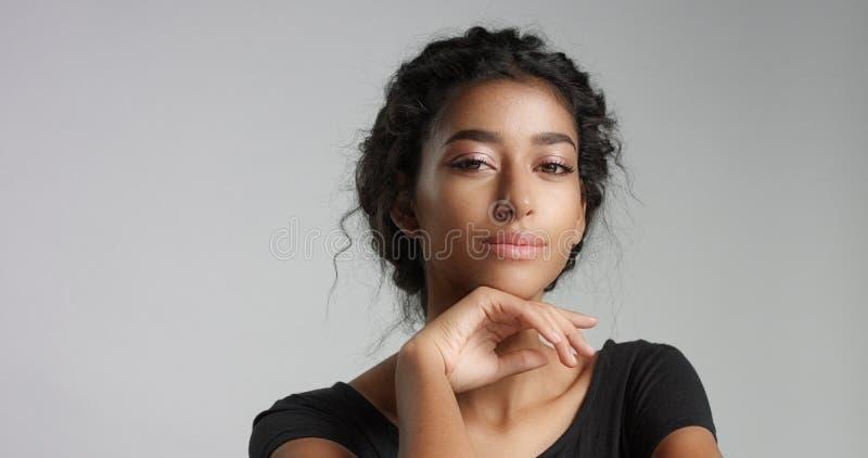 Jeune modèle du Moyen-Orient attrayant touchant son joli visage avec la peau impeccable photo stock