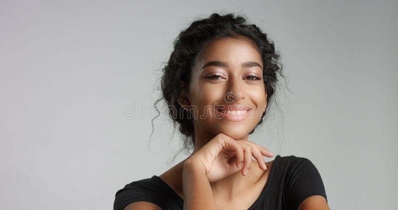 Jeune modèle du Moyen-Orient attrayant touchant son joli visage avec la peau impeccable images libres de droits