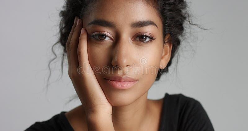 Jeune modèle du Moyen-Orient attrayant touchant son joli visage avec la peau impeccable photo libre de droits