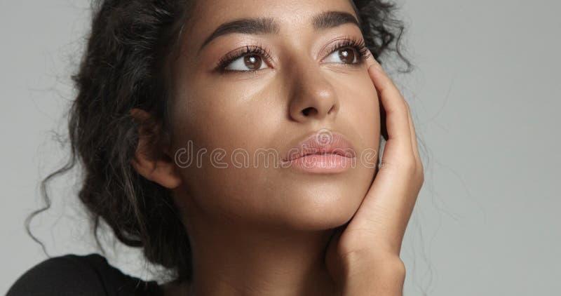 Jeune modèle du Moyen-Orient attrayant touchant son joli visage avec la peau impeccable image stock