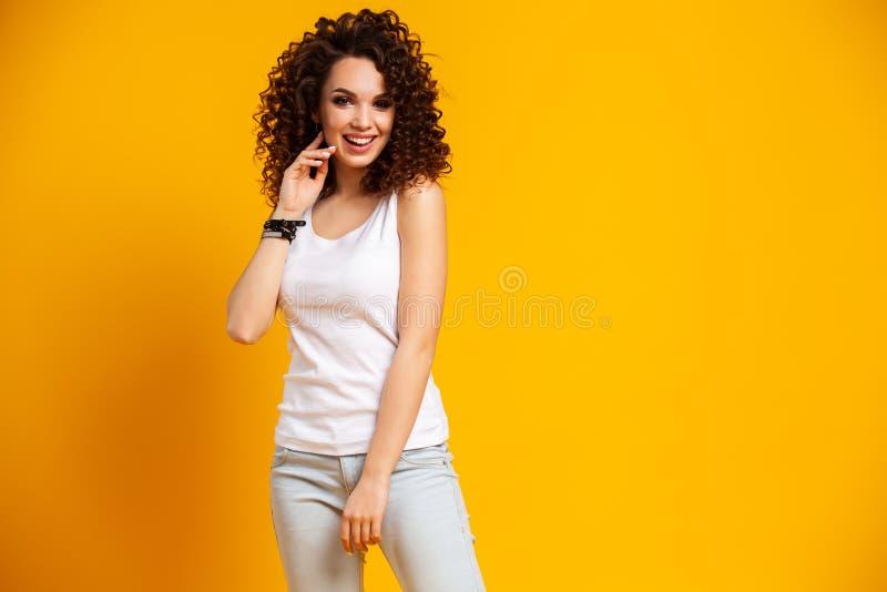 Jeune modèle exprimant des émotions tout en posant sur le photoshoot d'intérieur Femme bouclée élégante ayant l'amusement dans le photo libre de droits