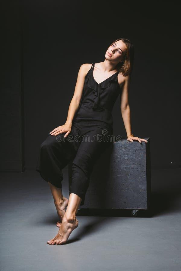 Jeune modèle femelle caucasien posant à l'arrière-plan de noir de studio Fille s'asseyant dans une robe noire sur un mur foncé su photo stock