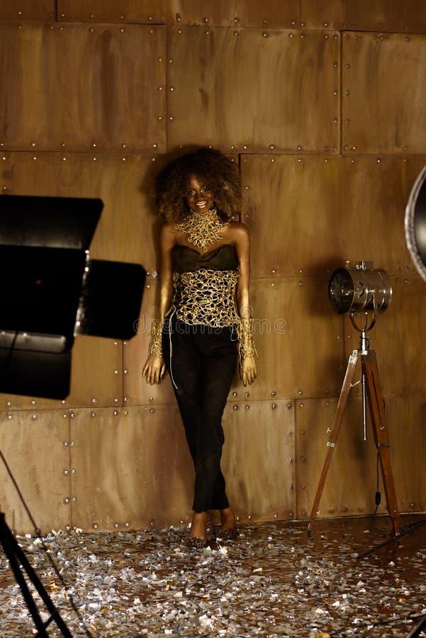 Jeune modèle femelle de sourire d'afro-américain se tenant au fond d'or et posant près des flashes de lumière de studio photos stock