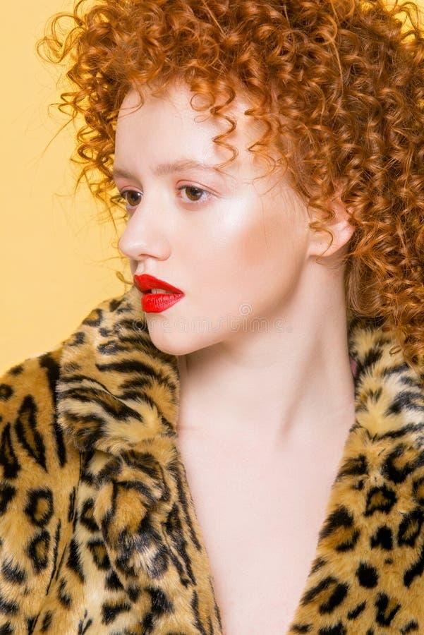 Jeune modèle lumineux avec des cheveux bouclés rouges et un manteau de tendance de léopard photo libre de droits