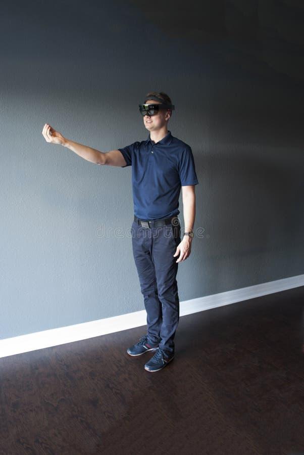 Jeune modèle masculin de sourire dans le casque de réalité virtuelle utilisant le regard fixe pour créer l'entourage 3d de mélang image libre de droits
