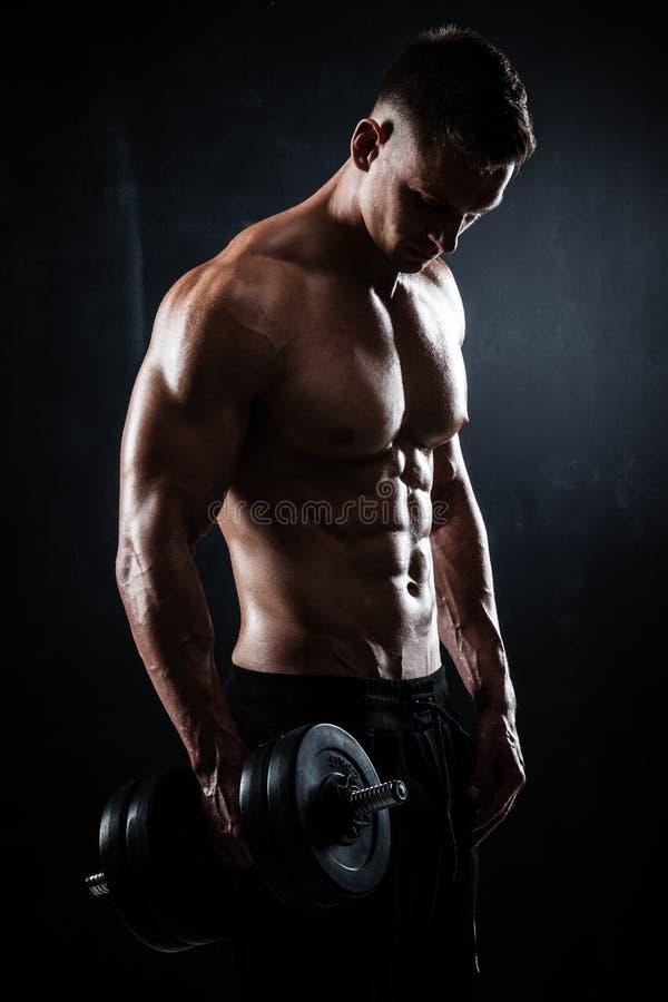 Jeune modèle masculin sans chemise sportif de forme physique avec des haltères photo stock