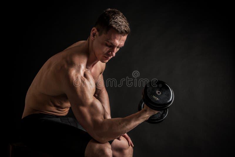 Jeune modèle masculin sans chemise sportif de forme physique avec des haltères photo libre de droits