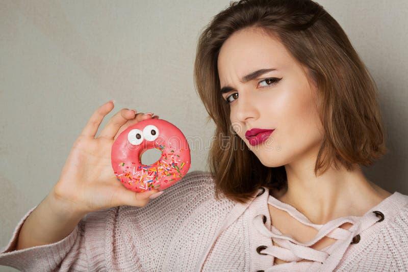 Jeune modèle suspect avec le beignet naturel de lustre de participation de maquillage au-dessus d'un fond gris L'espace pour le t photographie stock libre de droits