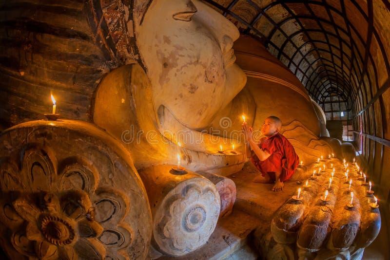 Jeune moine non identifié de bouddhisme priant avec la lumière de bougie photo libre de droits