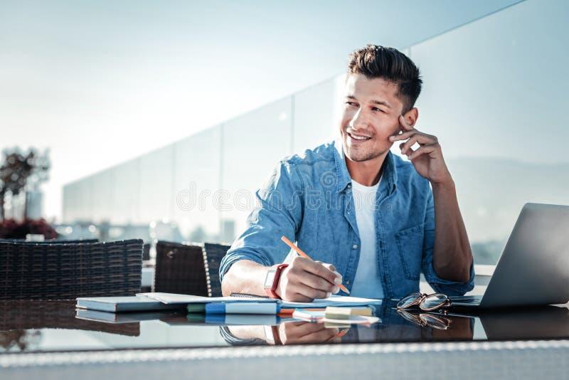 Jeune monsieur songeur souriant tout en travaillant sur l'ordinateur portable dehors photos libres de droits