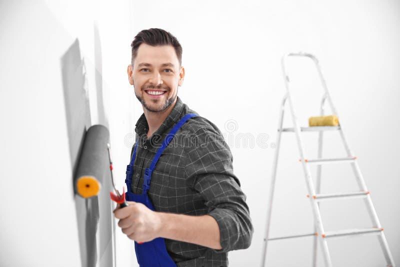 Jeune mur masculin de peinture de décorateur image stock