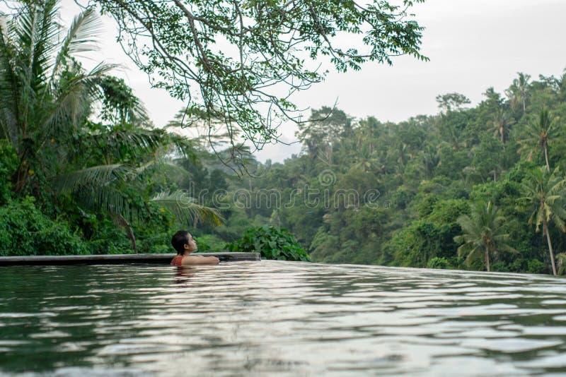 Jeune natation asiatique de fille dans la piscine d'infini avec la belle vue photo libre de droits