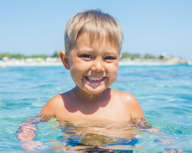 Jeune natation de garçon en mer photographie stock