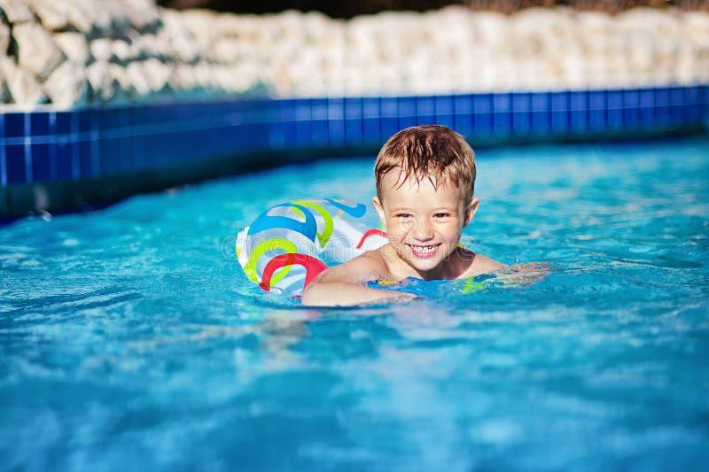 Jeune natation heureuse de garçon d'enfant dans la piscine avec l'anneau dans la station de vacances image stock