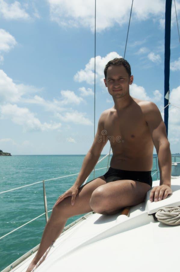 Jeune navigation adulte belle d'homme sur le yacht image stock