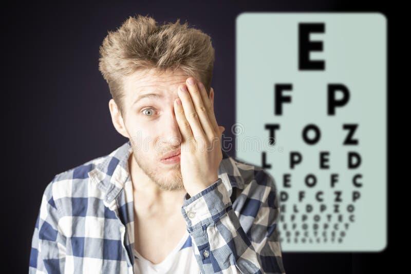 Jeune oeil masculin de vision et de couverture d'oeil d'essai avec la main b photographie stock
