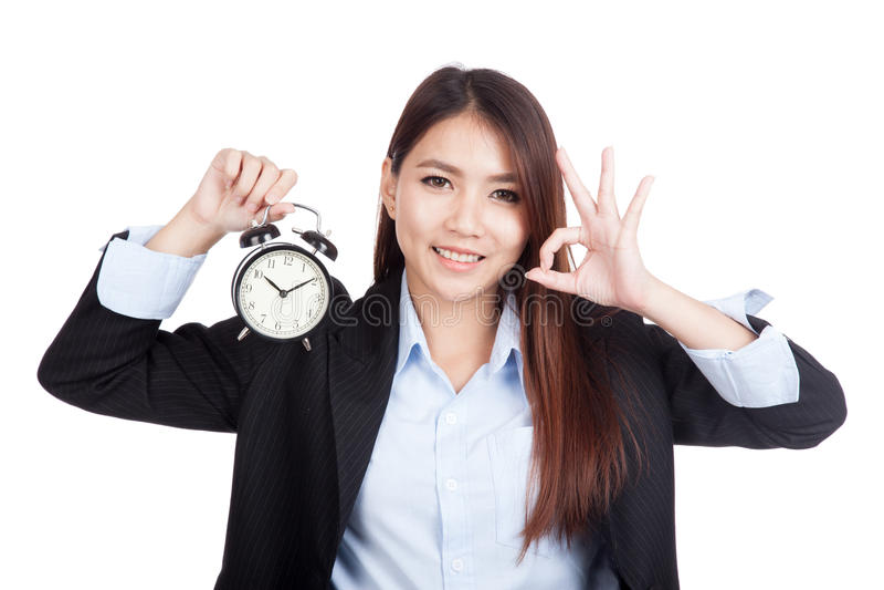 Jeune OK asiatique d'exposition de femme d'affaires avec le réveil photo stock