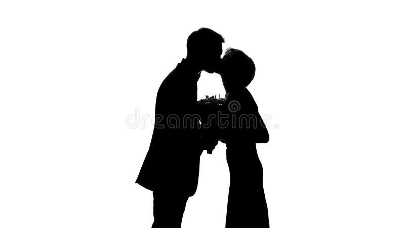 Jeune ombre de couples embrassant pendant la date romantique, ami donnant des fleurs photos libres de droits