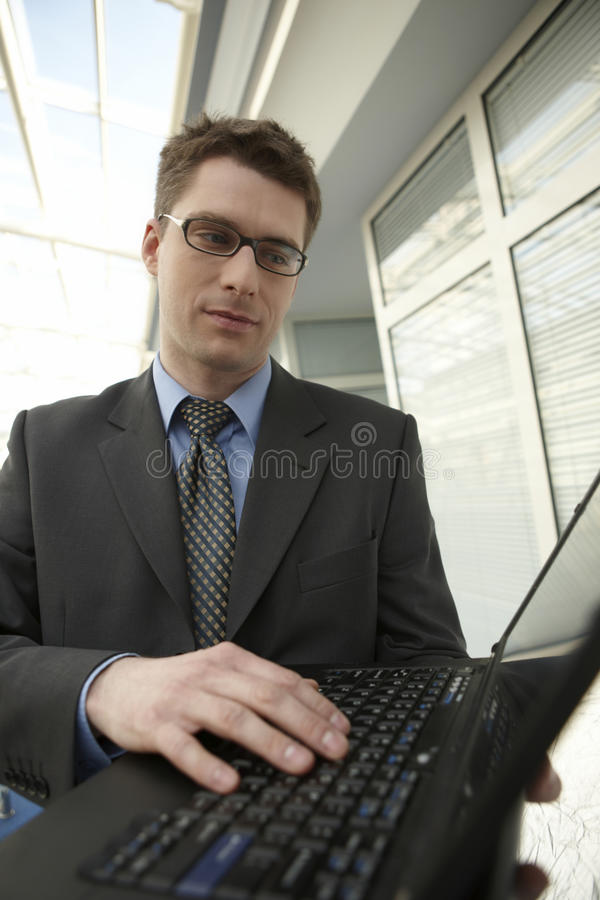 Jeune ordinateur portatif de sourire de bureaux d'homme d'affaires images libres de droits