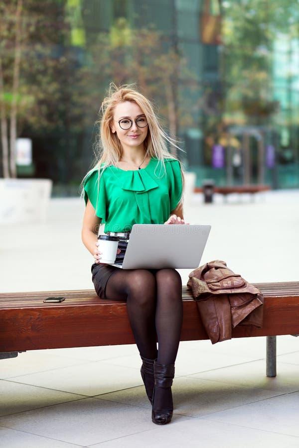Jeune oriental - femme d'affaires européenne marchant sur l'ordinateur portable sur la pause-café en dehors de l'immeuble de bure image libre de droits