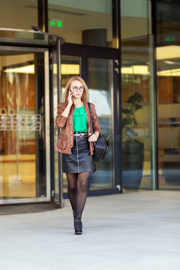 Jeune oriental - femme d'affaires européenne parlant au téléphone en dehors de l'immeuble de bureaux photo stock