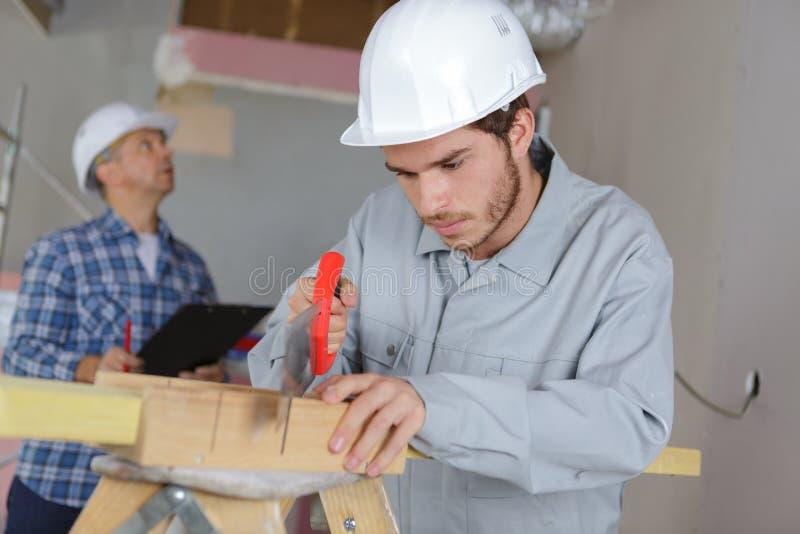 Jeune ouvrier employant le collègue supérieur de scie à main évaluant le site photographie stock libre de droits