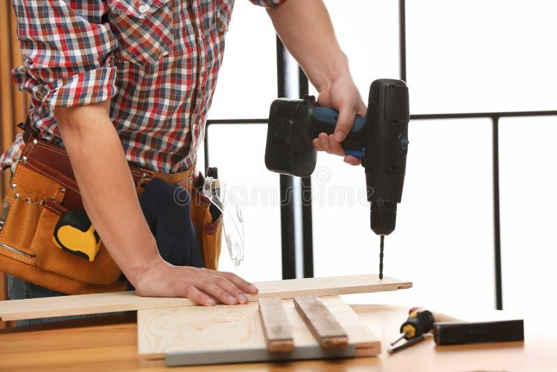 Jeune ouvrier utilisant la perceuse électrique à l'intérieur R?paration ? la maison photos libres de droits