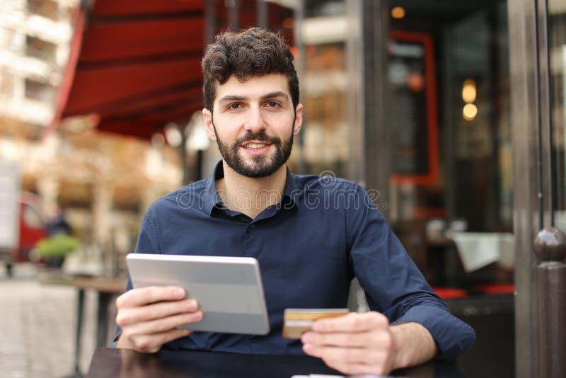 Jeune père achetant en ligne avec la carte par le smartphone au café dedans photographie stock