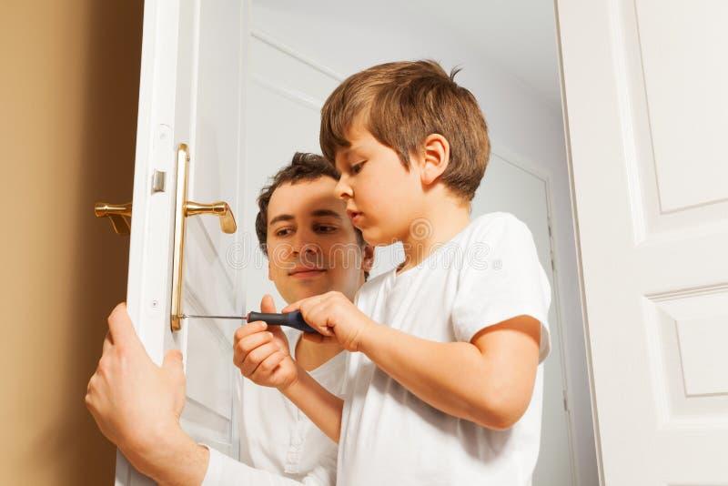 Jeune père aidant son fils à fixer la poignée de porte photos libres de droits