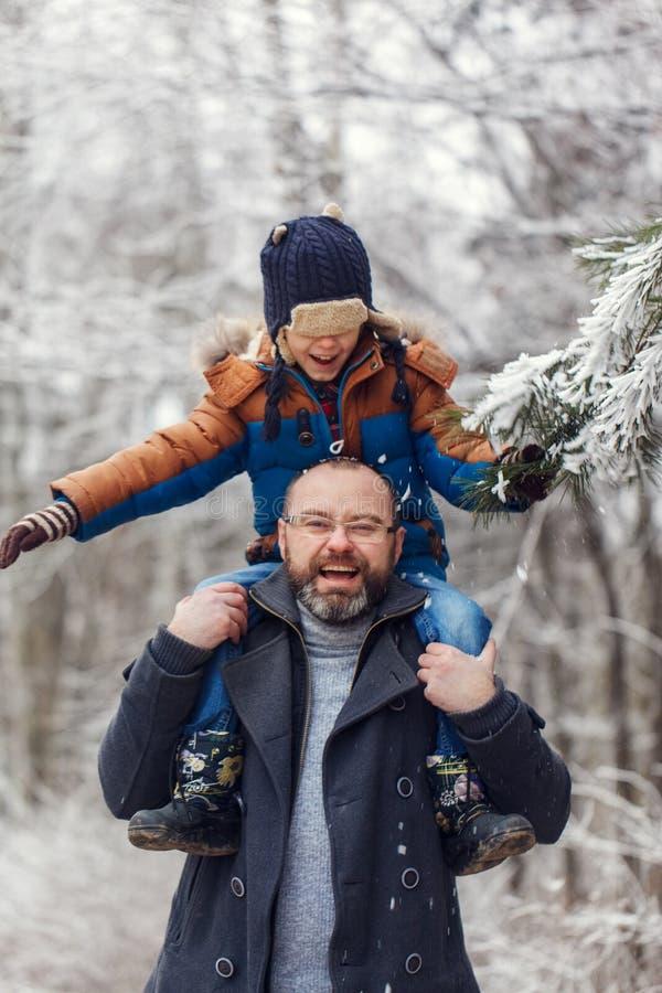 Jeune père barbu et l que peu de fils sur la promenade dans le garçon de forêt d'hiver se repose dans des épaules de l'homme Vaca image libre de droits