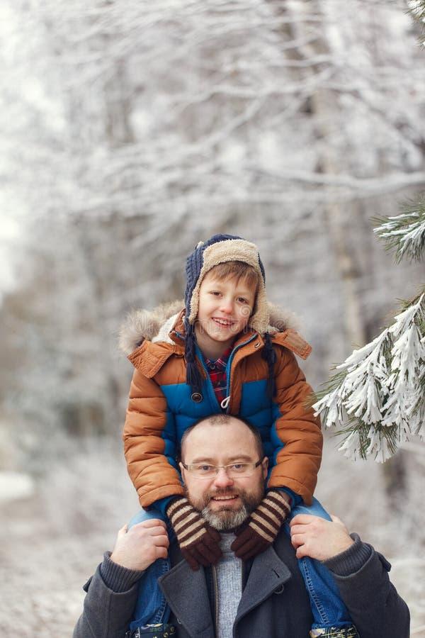 Jeune père barbu et l que peu de fils sur la promenade dans le garçon de forêt d'hiver se repose dans des épaules de l'homme Vaca photographie stock libre de droits