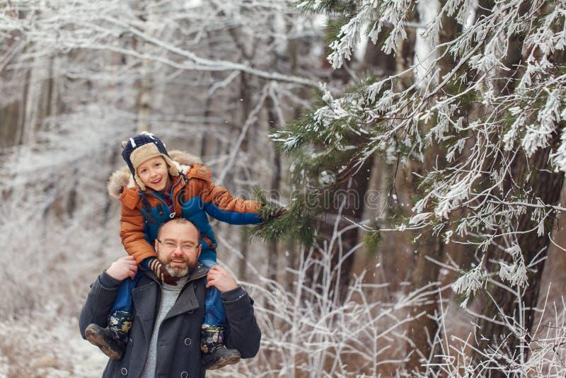 Jeune père barbu et l que peu de fils sur la promenade dans le garçon de forêt d'hiver se repose dans des épaules de l'homme Vaca photos stock