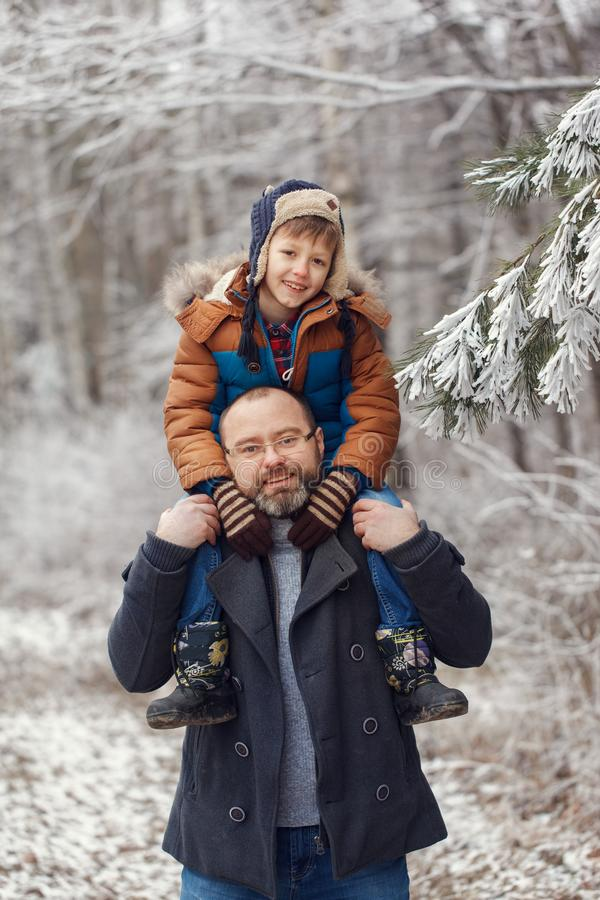 Jeune père barbu et l que peu de fils sur la promenade dans le garçon de forêt d'hiver se repose dans des épaules de l'homme Vaca photographie stock