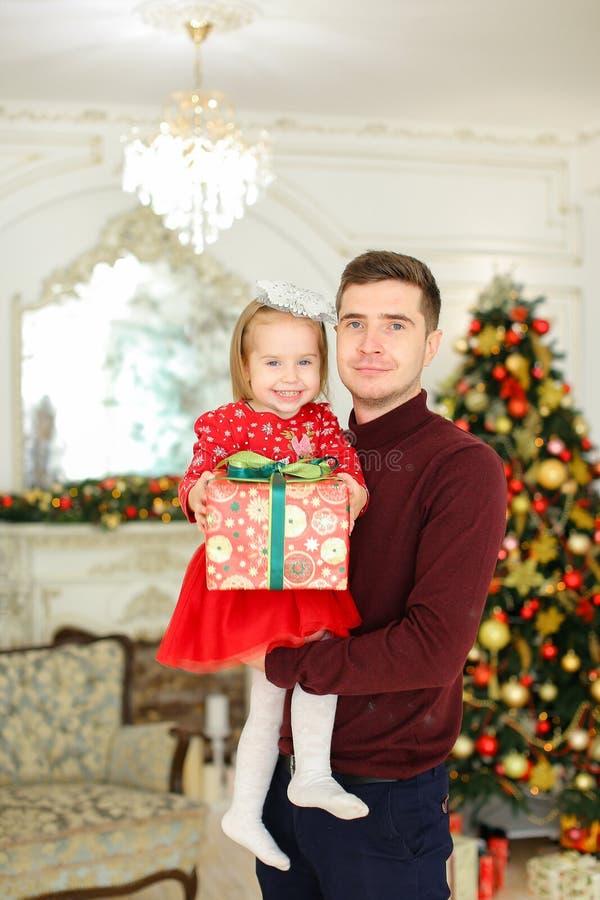 Jeune père caucasien gardant la petite fille avec le présent, arbre de Noël à l'arrière-plan image stock