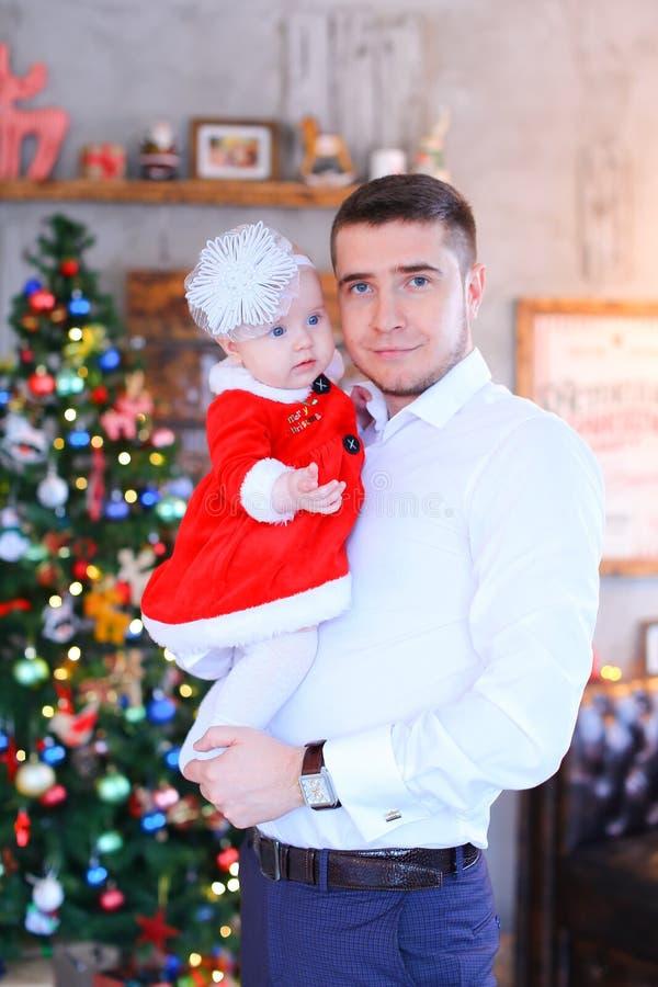 Jeune père caucasien maintenant la petite fille près de l'arbre de Noël dans le fond images stock