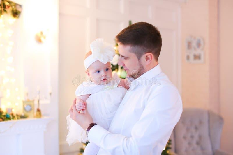Jeune père embrassant le petit bébé féminin et utilisant la chemise blanche image stock