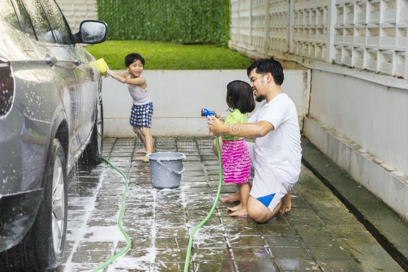 Jeune père enseignant ses enfants à laver la voiture photos libres de droits
