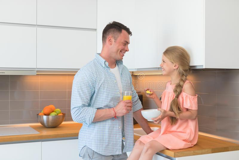 Jeune père et fille prenant le petit déjeuner photos stock
