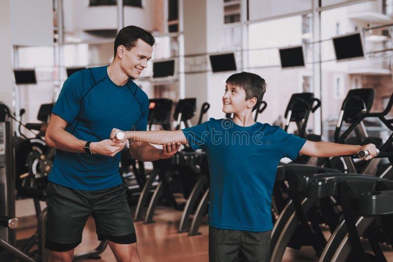 Jeune père et fils faisant des exercices dans le club de sport photo stock