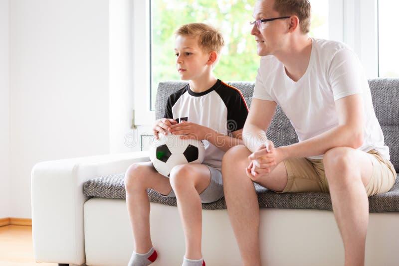 Jeune père et son championnat de observation du football du monde de fils avec images stock