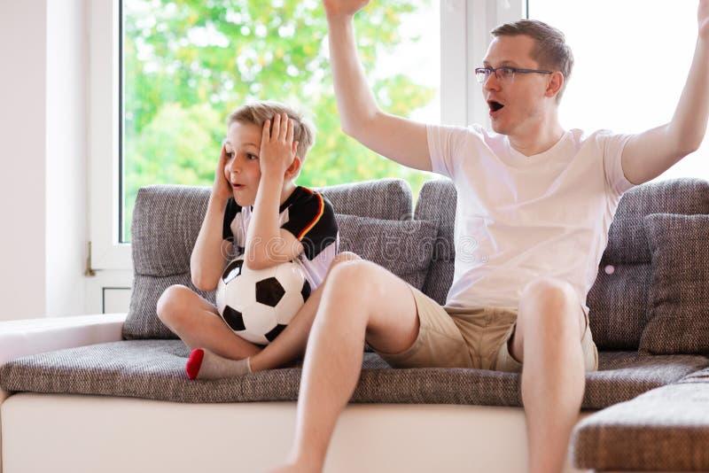 Jeune père et son championnat de observation du football du monde de fils avec photo stock