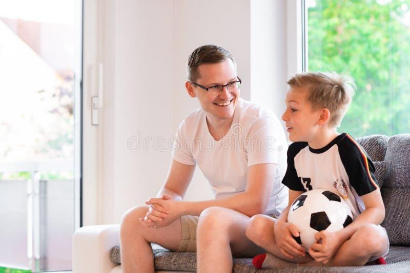 Jeune père et son championnat de observation du football du monde de fils avec image stock