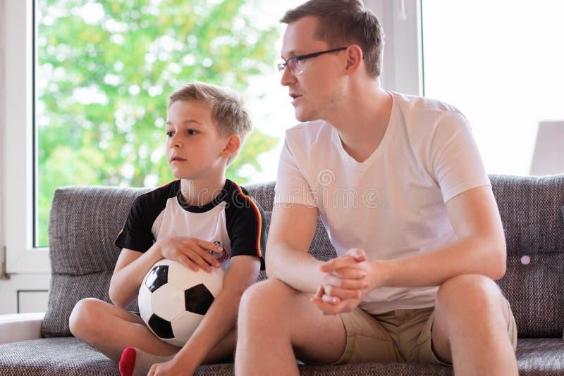 Jeune père et son championnat de observation du football du monde de fils avec photos libres de droits