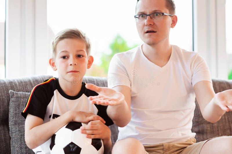 Jeune père et son championnat de observation du football du monde de fils avec images libres de droits