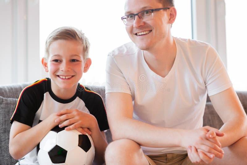 Jeune père et son championnat de observation du football du monde de fils avec photos stock